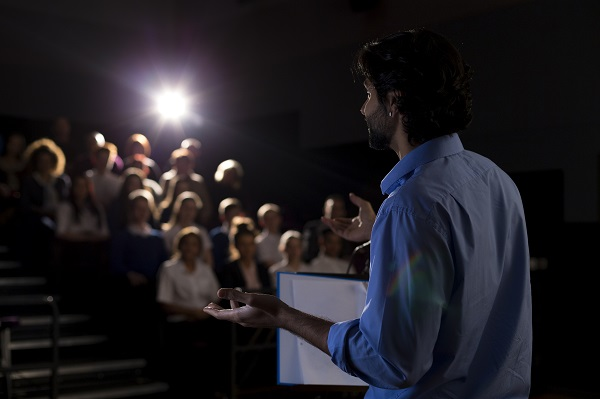 Male teacher giving a speech in a lecture hall to students and teachers.